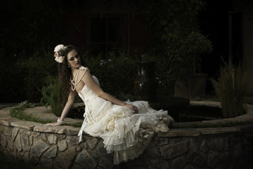 Beautiful vintage bride next to courtyard fountain