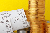 Cash register paper receipt check with coins stack closeup