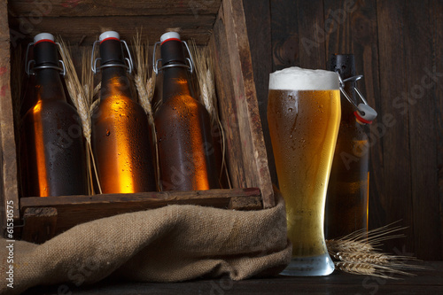 Beer glass with wooden crate full of beer bottles and wheat ears