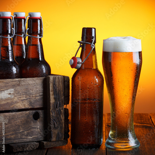 Beer glass with wooden crate full of beer bottles on table