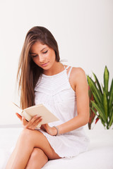 Beautiful young girl sitting on bed and reading