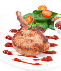 Juicy grilled pork fillet steak with greens