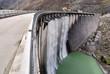 Leinwanddruck Bild - Water falls from the wall of the  dam
