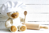 Teddy bear in chef hat with spoon abstract food background