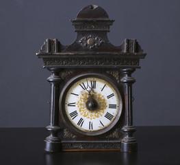 Vintage wooden clock on a dark background.