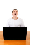 Teenager yawning behind Laptop