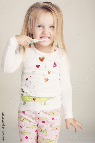 funny little girl in pyjamas with tooth brush