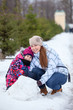 Happy mother with daughter sit in snow with snowball at winter