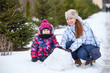 Happy mother with child looking at camera at snow, winter park