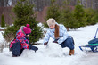 Happy mother and child building snowman in winter park