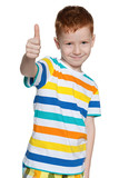 Red-haired little boy holds his thumb up
