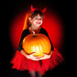 little halloween devil girl holding big pumpkin