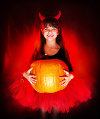 smiling little halloween devil girl holding big pumpkin