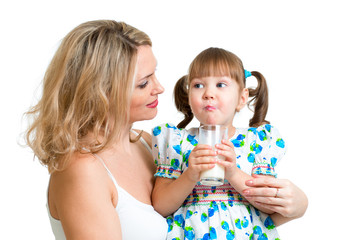 Kid drinking milk. Mother looks to daughter.