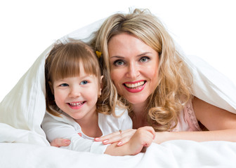 happy mother and child lying under the blanket
