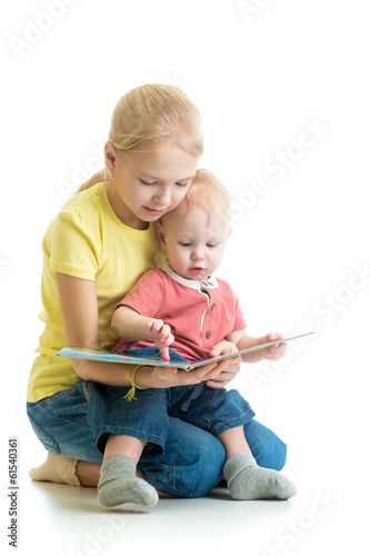 kid girl playing reading book to her little brother