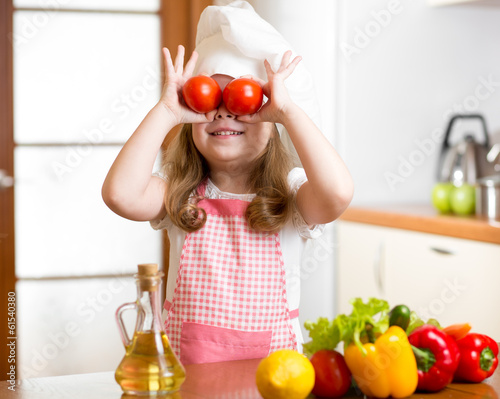 Funny chef girl preparing healthy food at kitchen