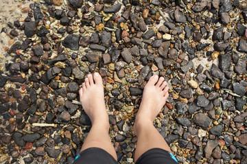 pebble barefoot, female two feet barefoot on pebble ground beach