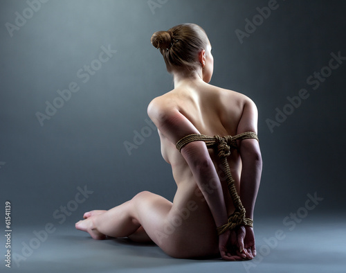 Rear view of nude slim woman tied with rope
