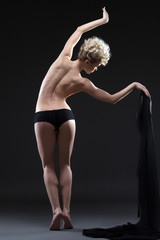 Flexible young woman dancing topless with cloth