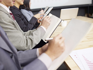 business people taking notes during meeting