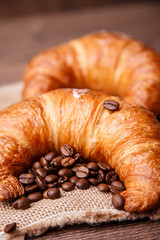 Two croissants and coffee beans on a linen napkin