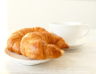Two croissants and a clean white cup
