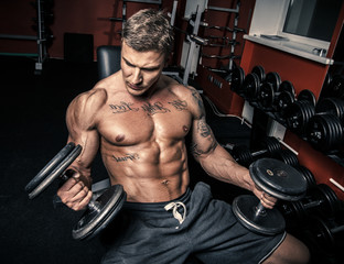 Tattooed bodybuilder with two dumbbells