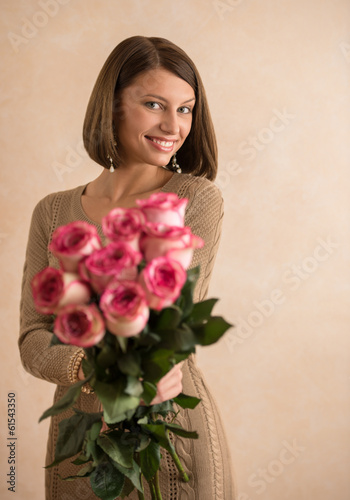 Beautiful woman with a large bouquet of flowers in her arms