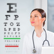 Female optician standing in front of eyesight test at hospital