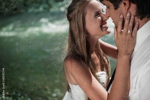 Beautiful wedding couple hugging and smiling on the river