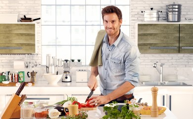 Handsome man cooking in kitchen at home