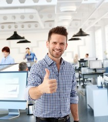 Casual man showing thumb-up in office