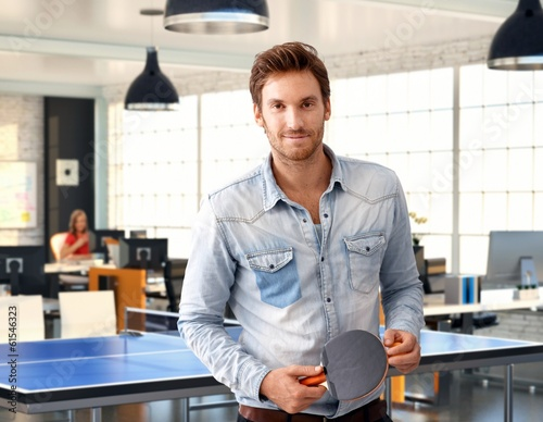 Casual man holding ping-pong racket at office