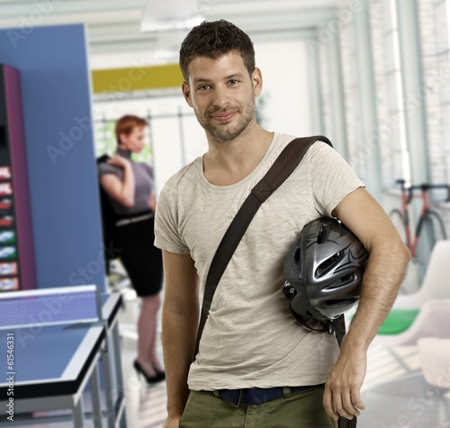 Casual young man arriving to work by bicycle