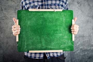 Man holding green chalkboard