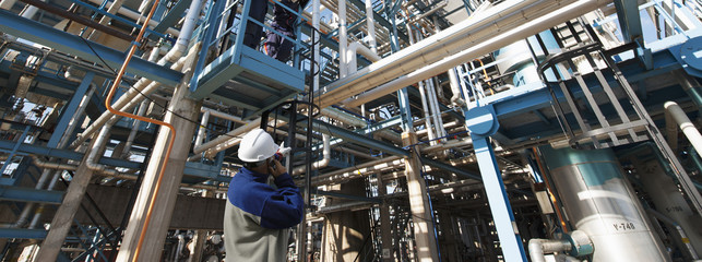 refinery worker pointing at distillery inside refinery