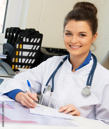 Cheerful young doctor woman in her office behind table