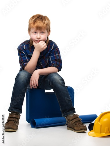 Bored little mechanic boy sitting on a toolbox