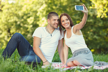 Young couple taking a self portrait in the park