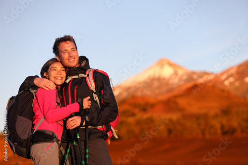 Happy couple hiking enjoying looking at view