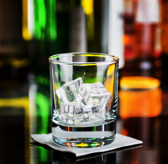 Glass with ice cubes on a bar desk