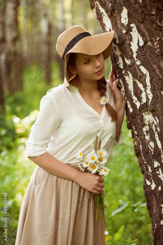 Beautiful woman with a bouquet of daisies near birch