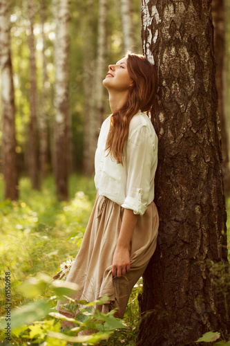 Woman leaning against birch and resting