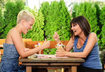 Two young women eating fruit salad