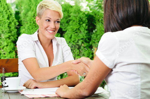 Two women face to face at a business meeting handshaking