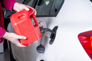 Red gas can adds fuel to an automobile