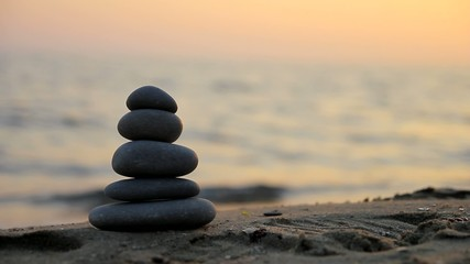 Stacked stones on the beach at sunset