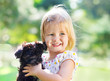 Cute little girl hugging dog puppy outdoors