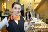 Waitress presenting cake in cafe or confectionery